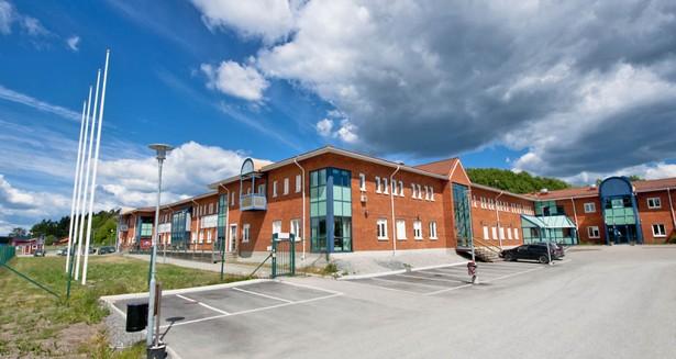 Näsvägen 15 i Runö, Åkersberga, med lokalens befintliga entré till vänster om bilarna